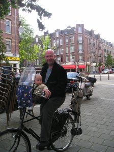 Author with infant son on his bicycle
